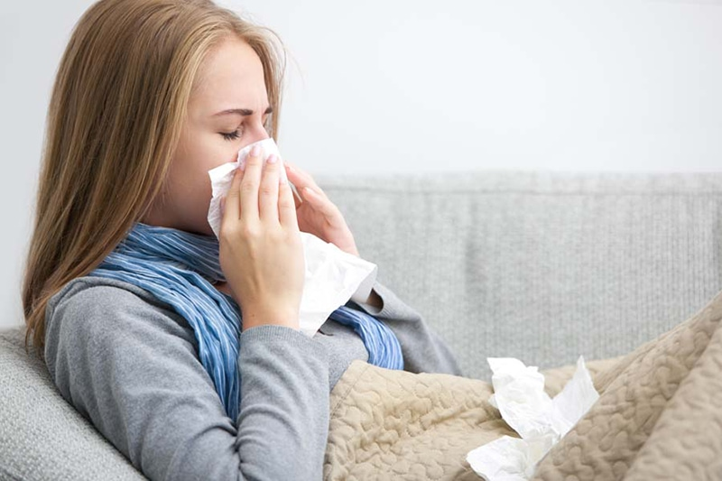 Does an AC Help With Allergies? Close up of a young woman sneezing into a tissue.