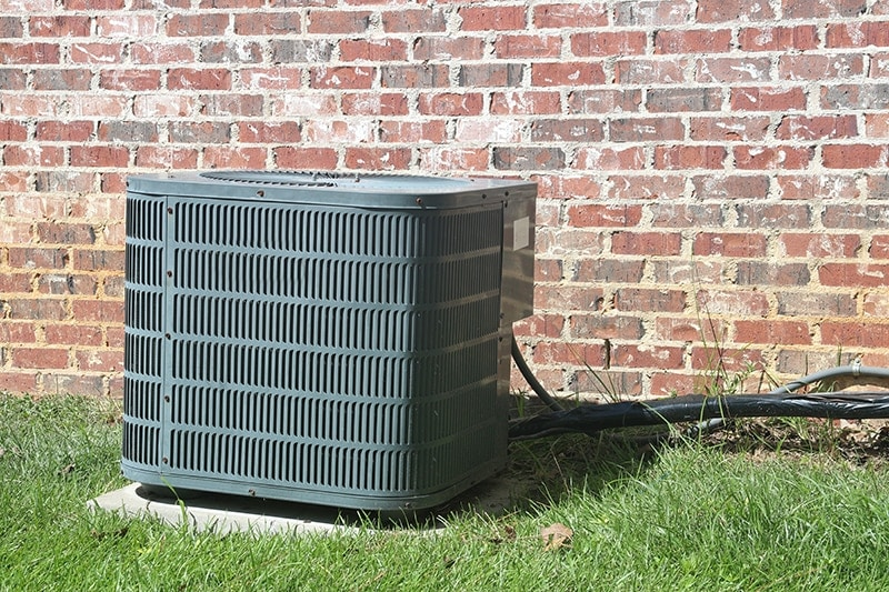 Home Air Conditioner Condenser coil sitting in front of brick wall
