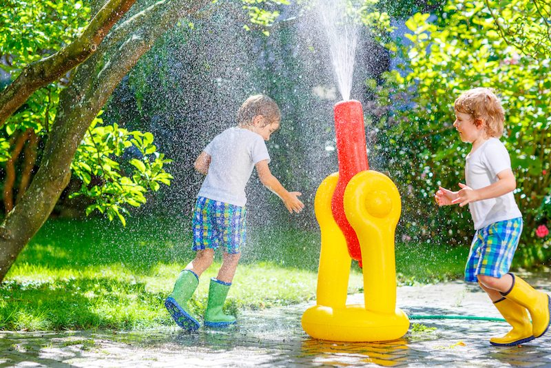 Two boys running through a sprinkler and are managing humidity in Athens