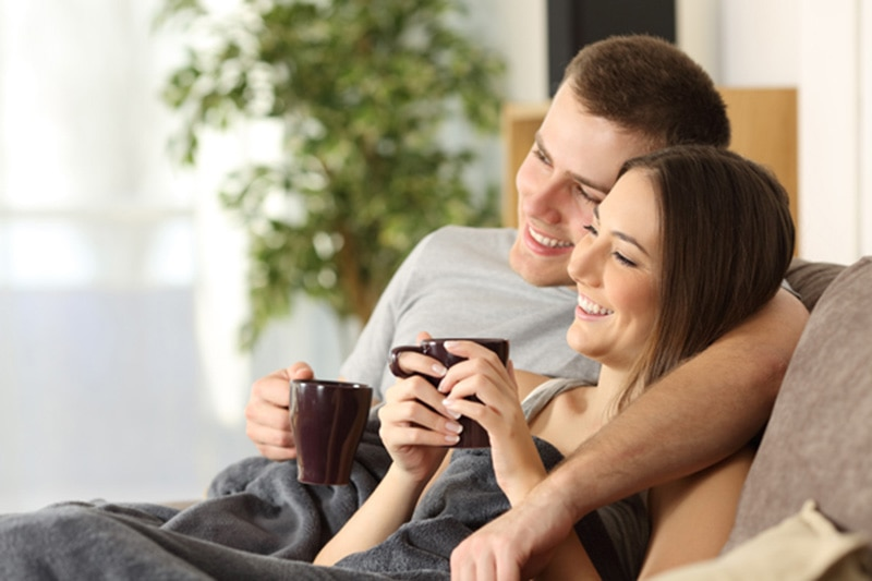 happy young couple relaxing with mugs under a blanket on their couch at home. How Can I Make My Furnace Last Longer?