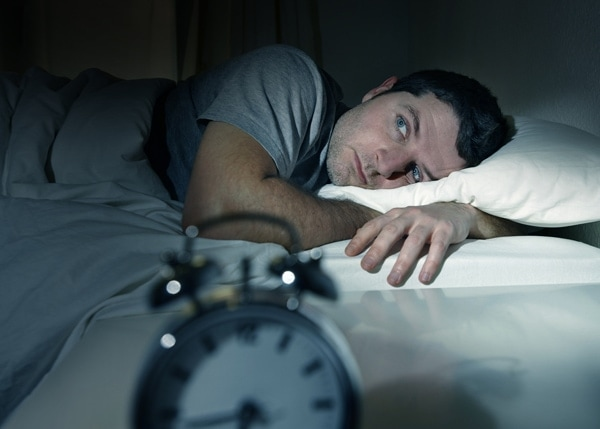 Man trying to sleep after realizing the loud sound coming from his furnace.