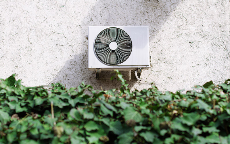 A central air conditioning unit mounted on the wall of an Athens