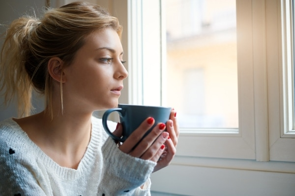 Girl feeling in a bad mood and drinking hot drink.