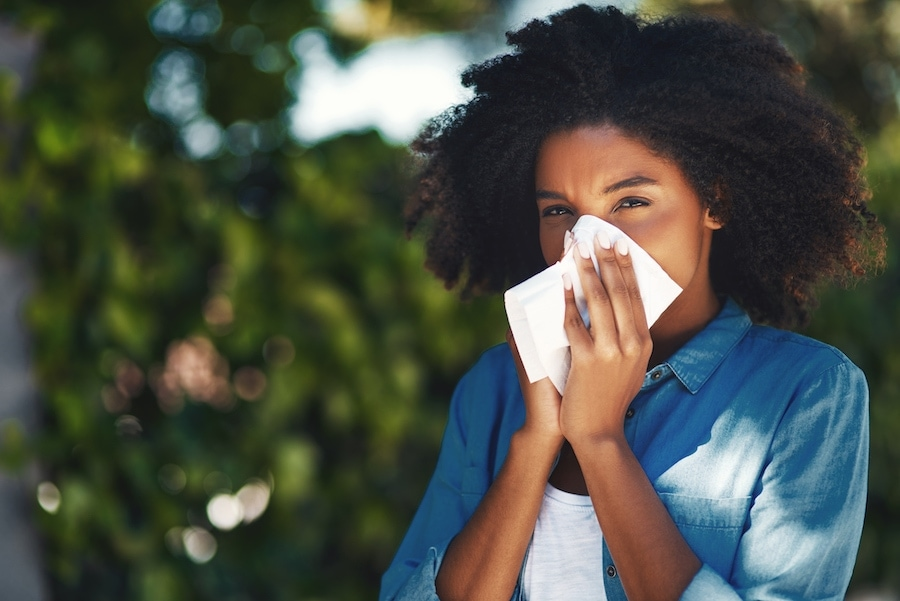 Woman blowing nose due to allergies
