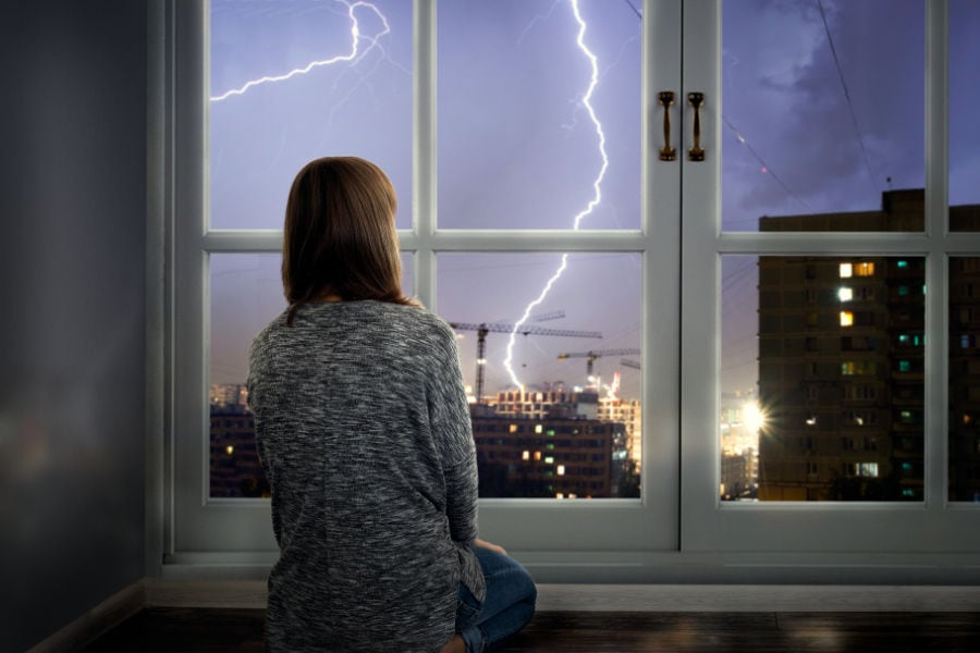 Woman looking out window at storm after losing power and learning how to get your home generator running quickly and safely.