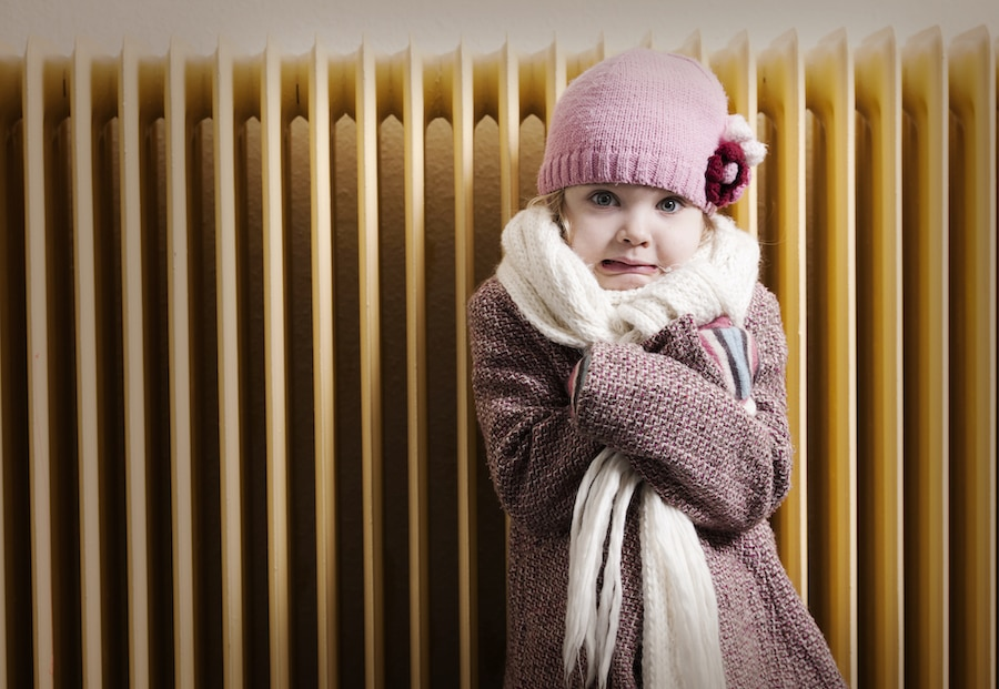 Girl trying to stay warm inside after realizing her furnace isn't heating her entire home.