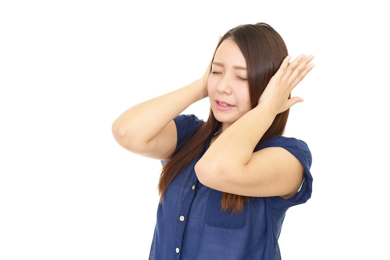 Woman covering her ears with closed eyes. Her air conditioner is making too much noise.