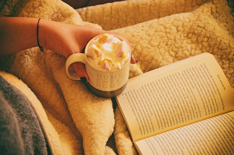 A person is reading a book and drinking hot chocolate in Belpre