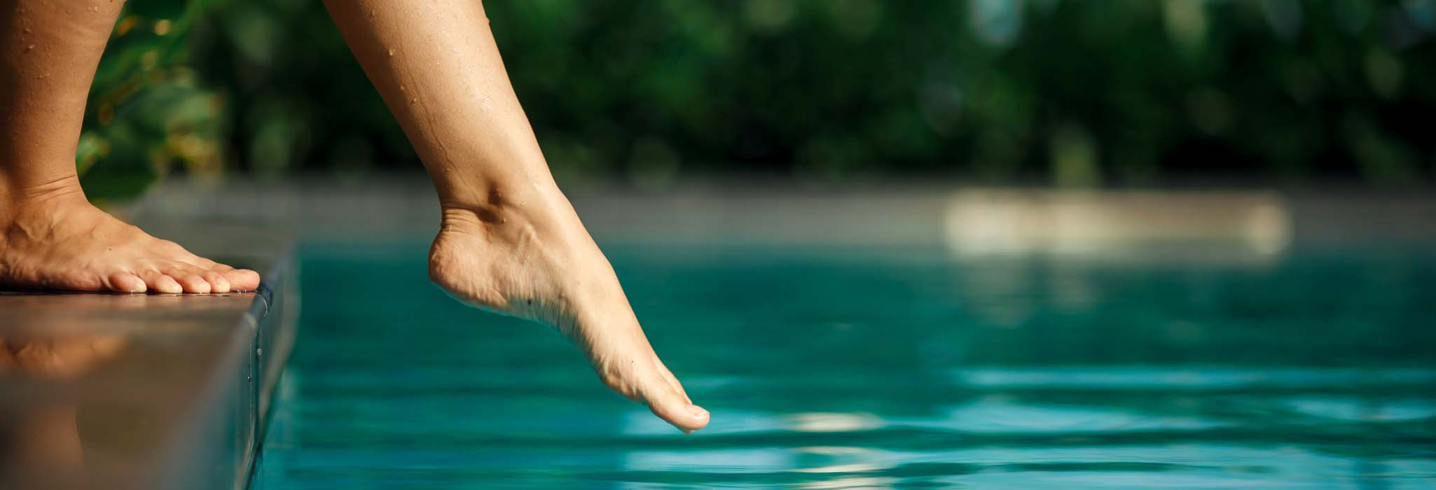 Closeup young female leg touch blue water in swimming pool.