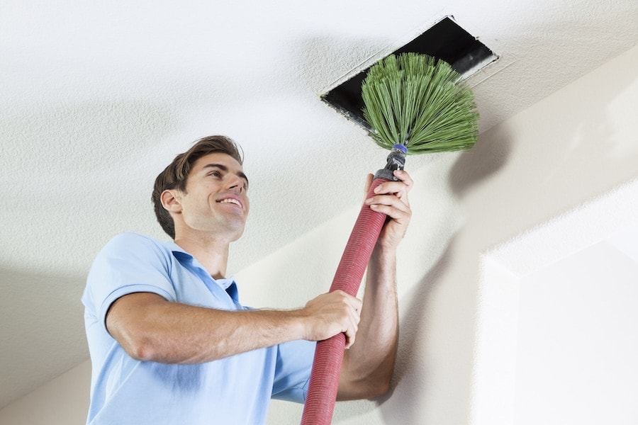 technician cleaning air ducts in home to rid of mold